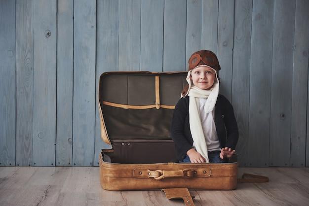 Szczęśliwy dzieciak w pilotowym kapeluszu bawić się z starą walizką. dzieciństwo. fantazja, wyobraźnia. wakacje Premium Zdjęcia