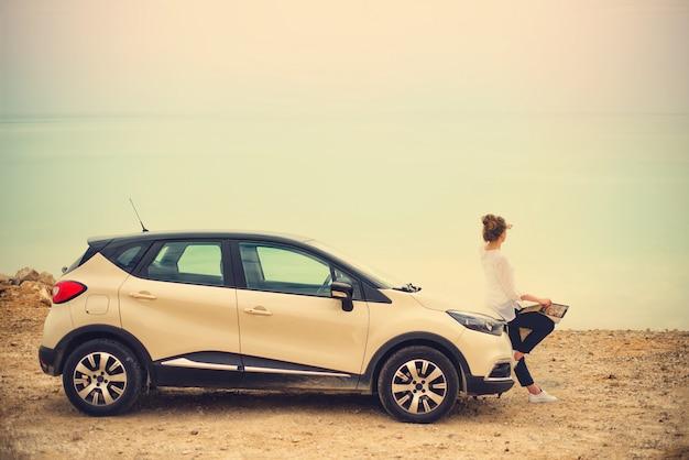 Szczęśliwy elegancki młoda kobieta podróżnik na plażowym drogowym obsiadaniu na białym skrzyżowaniu samochodu Premium Zdjęcia