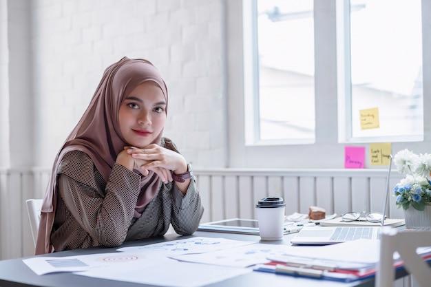 Szczęśliwy Fachowy Arabski Bizneswomanu Brązu Hijab Pracuje W Domu. Premium Zdjęcia