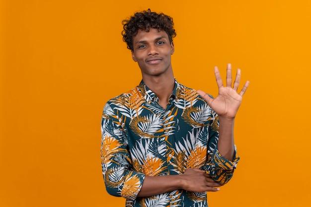 Szczęśliwy I Pozytywnie Nastawiony Młody Przystojny Ciemnoskóry Mężczyzna Z Kręconymi Włosami W Koszulce Z Nadrukiem Liści I Pokazujący Palcami Numer Pięć Darmowe Zdjęcia
