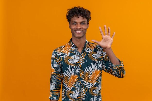 Szczęśliwy I Uśmiechnięty Młody Przystojny Ciemnoskóry Mężczyzna Z Kręconymi Włosami W Liściach Drukowanej Koszuli, Pokazując Palcami Numer Pięć Darmowe Zdjęcia