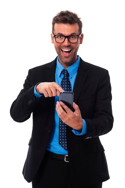 Szczęśliwy I Zdziwiony Biznesmen, Wskazując Na Telefon Komórkowy Darmowe Zdjęcia