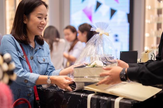 Szczęśliwy kobieta klienta otrzymujący prezent i kwiatu pudełko ustawiający od kierownika sklepu. Premium Zdjęcia