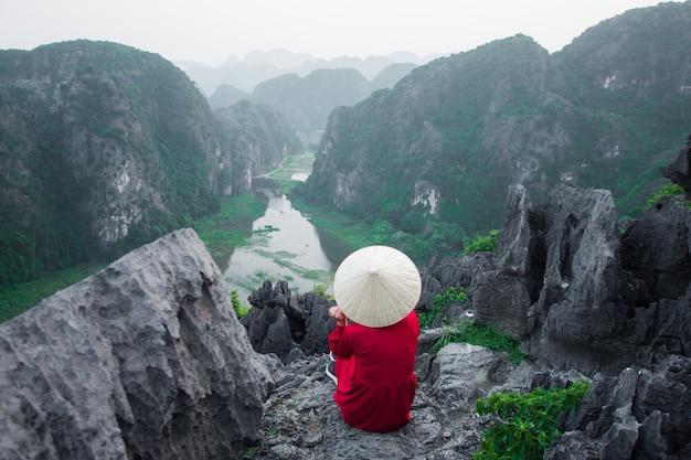Szczęśliwy Kobieta Stojak Na Szczycie Góry Przy Mua Cave, Ninh Binh, Wietnam Przy Wieczór, Temat Jest Zamazany, Niski Klucz I Hałas. Premium Zdjęcia