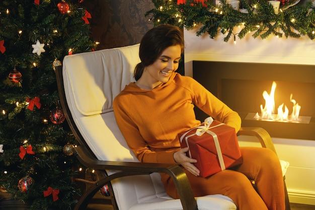 Szczęśliwy kobiety obsiadanie w bujanym krześle obok kominka Premium Zdjęcia