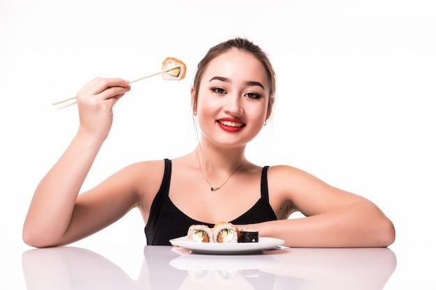 Szczęśliwy ładny Azjatykci Spojrzenie Z Skromną Fryzurą Siedzi Na Stole Je Suszi Rolek Ono Uśmiecha Się Odizolowywam Na Bielu Darmowe Zdjęcia