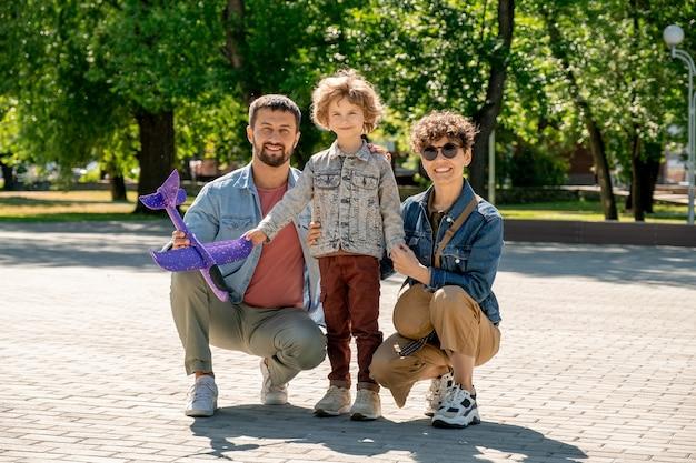 Szczęśliwy ładny Mały Chłopiec I Jego Kochający Młodzi Rodzice W Casualowych Ubraniach, Patrząc Na Ciebie, Spędzając Czas W Publicznym Parku W Słoneczny Dzień Premium Zdjęcia