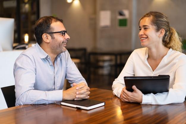 Szczęśliwy menedżer dorosłych połowie rozmowy z młodym klientem kobiece Darmowe Zdjęcia