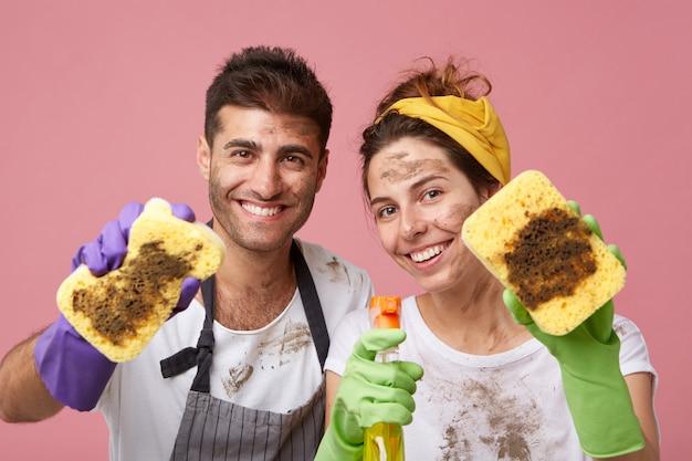 Szczęśliwy Mężczyzna I Kobieta Uśmiechając Się Szeroko, Trzymając Brudne Gąbki I Spray Do Prania, Ciesząc Się Z Mycia Mebli W Domu. Darmowe Zdjęcia