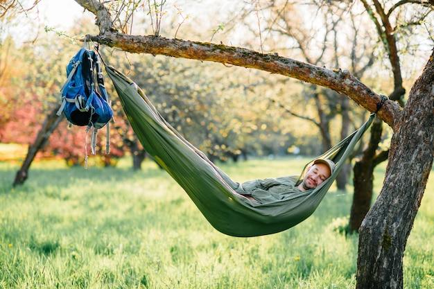 Szczęśliwy Mężczyzna Relaksuje W Hamaka Obwieszeniu Na Jabłoni W Lato Pogodnym Parku. Premium Zdjęcia