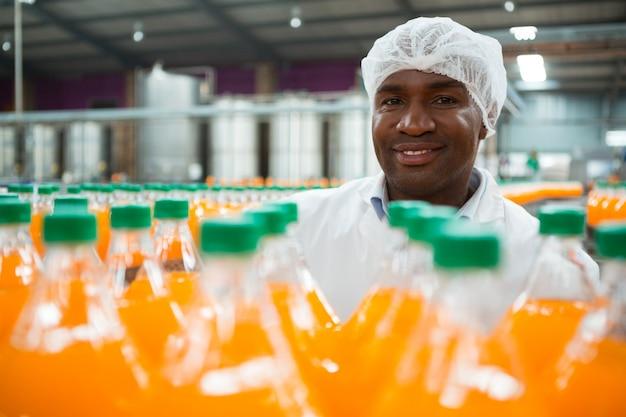 Szczęśliwy Mężczyzna Robotnik Stojący Przy Butelkach Soku Pomarańczowego W Fabryce Darmowe Zdjęcia