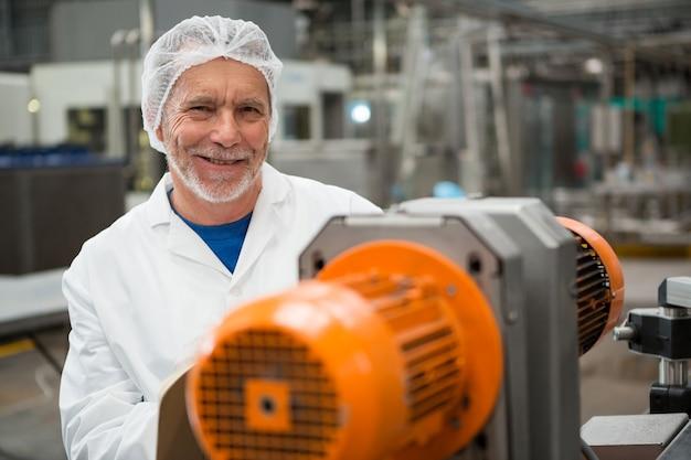 Szczęśliwy Mężczyzna Robotnik Stojący Przy Maszynach W Fabryce Zimnych Napojów Darmowe Zdjęcia