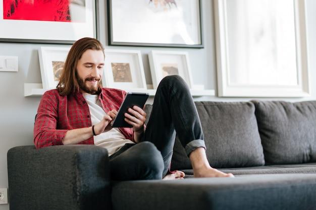 Szczęśliwy Mężczyzna Siedzi Na Kanapie I Używa Pastylkę W Domu Darmowe Zdjęcia