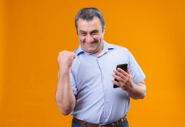 Szczęśliwy Mężczyzna W średnim Wieku W Niebieskiej Koszuli W Pionowe Paski I Podnoszący Rękę W Geście Zaciśniętej Pięści Darmowe Zdjęcia