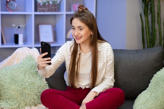 Szczęśliwy Młodej Kobiety Blogger Influencer Trzyma Nowożytną Mądrze Telefon Fala Rękę Cześć. Uśmiechnięta Vlogger Dziewczyna Patrzeje Wiszącą Ozdobę Robi Rozmowie Wideo, Strzelający Vlog Bierze Selfie Odizolowywającego Na Domowym Tle Premium Zdjęcia
