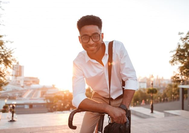 Szczęśliwy Młody Afrykański Mężczyzna W Wczesnym Poranku Z Bicyklem Darmowe Zdjęcia