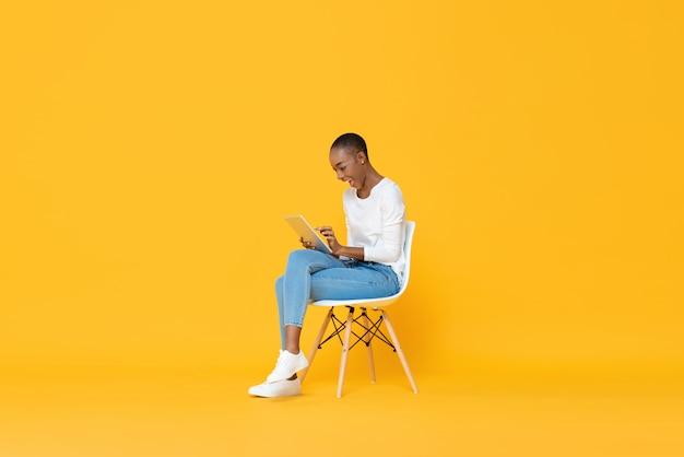 Szczęśliwy Młody Amerykanin Afrykańskiego Pochodzenia Kobiety Obsiadanie Na Krześle Używa Pastylka Komputer Premium Zdjęcia