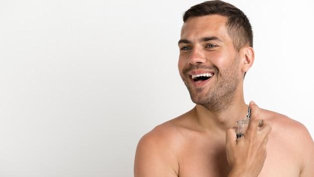 Szczęśliwy Młody Bez Koszuli Mężczyzna Opryskiwania Pachnidła Stoi Przeciw Białemu Tłu Darmowe Zdjęcia