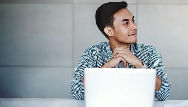 Szczęśliwy młody biznesmen pracuje na komputerowym laptopie w biurze Premium Zdjęcia