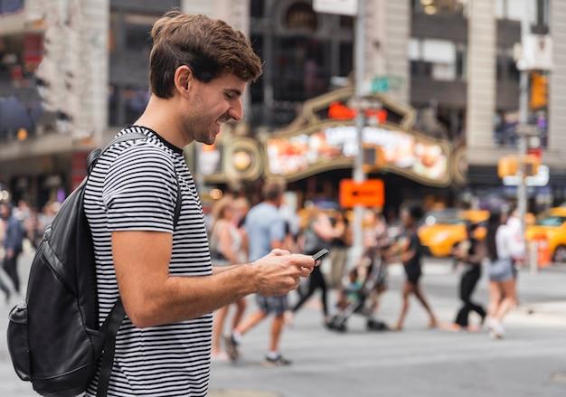 Szczęśliwy młody człowiek patrzeje smartphone Darmowe Zdjęcia