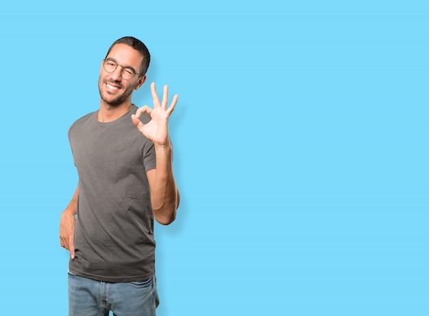 Szczęśliwy młody człowiek robi dobrze gest Premium Zdjęcia
