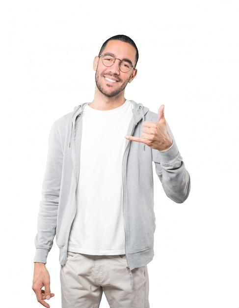 Szczęśliwy Młody Człowiek Robi Gestowi Dzwonić Z Ręką Premium Zdjęcia