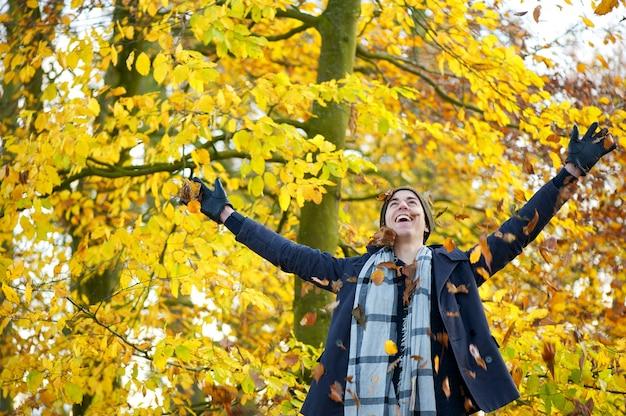 Szczęśliwy młody człowiek uśmiecha się liście z otwartymi rękami i rzuca Premium Zdjęcia