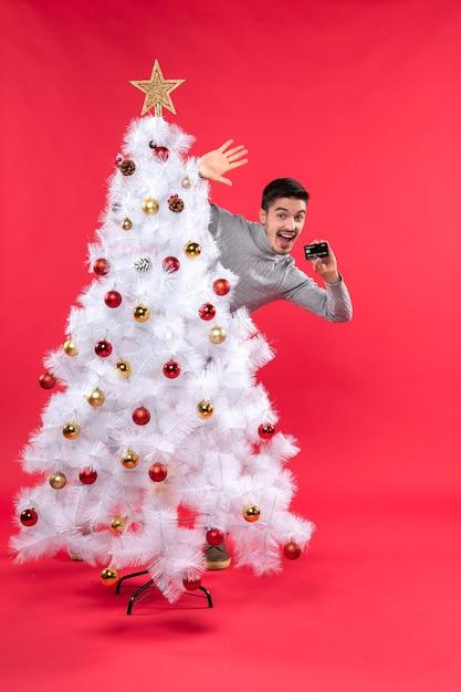 Szczęśliwy Młody Dorosły Stojący Za Zdobionym Drzewem Xmas I Trzymając Telefon Na Czerwono Darmowe Zdjęcia