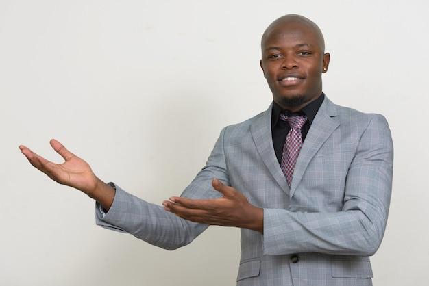 Szczęśliwy Młody łysy Biznesmen Afrykański Pokazuje Coś Premium Zdjęcia