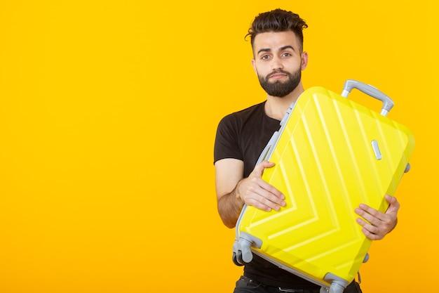 Szczęśliwy Młody Mężczyzna Hipster Z Brodą, Trzymając żółtą Walizkę Na żółtej Powierzchni I Radując Się Premium Zdjęcia