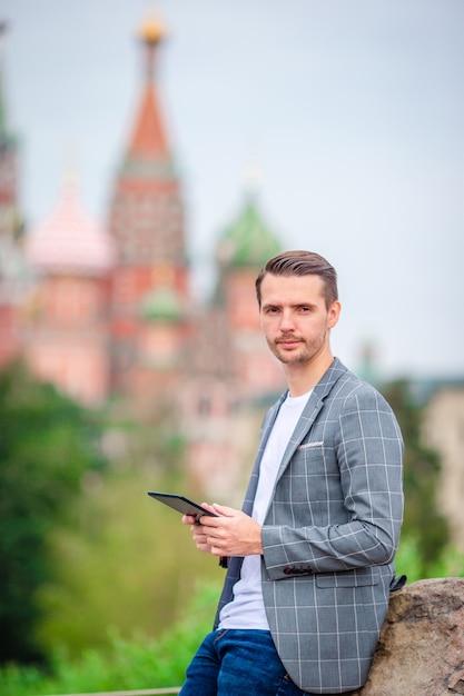 Szczęśliwy młody miastowy mężczyzna pije kawę w europejskim mieście. Premium Zdjęcia