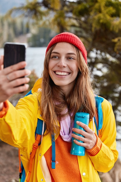 Szczęśliwy Młody Podróżnik Uśmiecha Się Radośnie, Robi Selfie Z Telefonem Komórkowym, Ubrany W żółtą Kurtkę, Trzyma Termos Z Herbatą, Odpoczywa W Pięknym Lesie Darmowe Zdjęcia