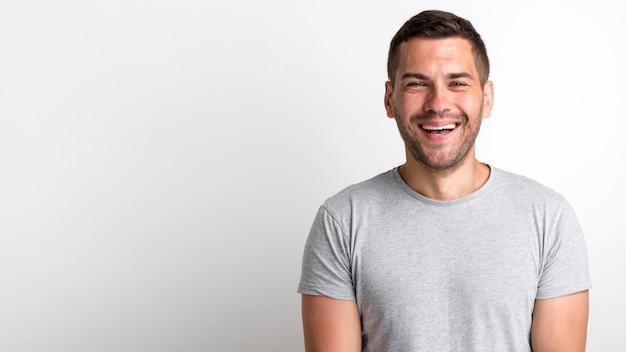 Szczęśliwy młody ścierniskowy mężczyzna śmia się i stoi nad białym tłem Darmowe Zdjęcia