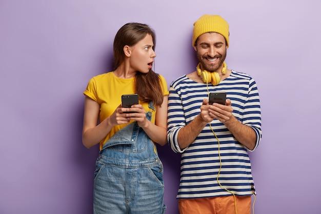 Szczęśliwy Młodzieniec Czyta Posty Na Portalach Społecznościowych, Nosi Słuchawki, Sweter W Paski, Trzyma Nowoczesny Telefon Komórkowy, Wściekła Kobieta Darmowe Zdjęcia