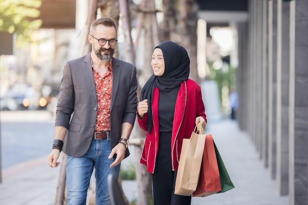 Szczęśliwy Muzułmański Przyjaciel Kobieta I Chłopiec Z Ręki Zakupy Miasta Trzymając Papierowe Torby Premium Zdjęcia