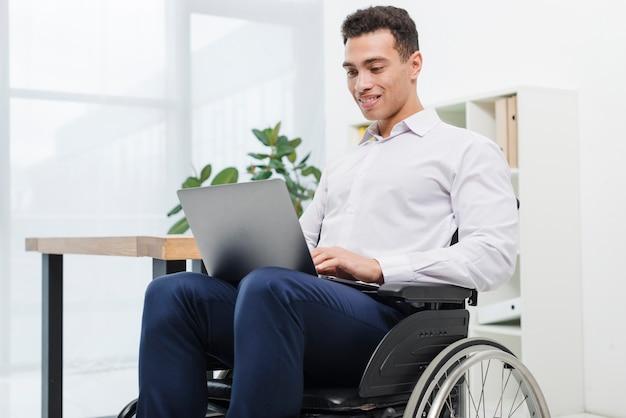 Szczęśliwy niepełnosprawny młody biznesmen siedzi na wózku inwalidzkim używać laptop w biurze Darmowe Zdjęcia