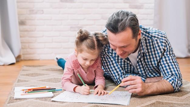 Szczęśliwy ojciec i córka rysuje wpólnie w domu Darmowe Zdjęcia