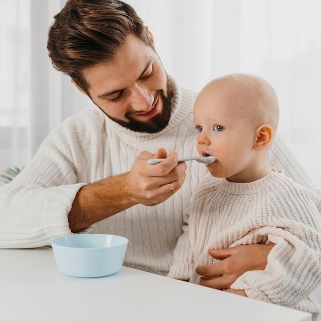 Szczęśliwy Ojciec Karmi Swoje Dziecko Premium Zdjęcia
