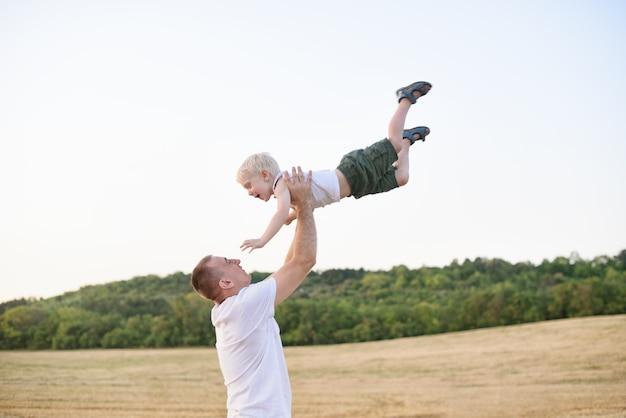 Szczęśliwy ojciec rzuca małego blond chłopca na skoszone pole pszenicy. czas zachodu słońca Premium Zdjęcia