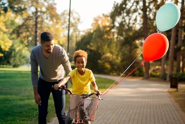 Szczęśliwy Ojciec Uczy Swoją Uroczą Córkę Jeździć Na Rowerze W Parku Darmowe Zdjęcia