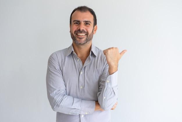 Szczęśliwy optymistycznie przystojny łaciński kierownik sprzedaży wskazuje na boku i patrzeje kamerę. Darmowe Zdjęcia