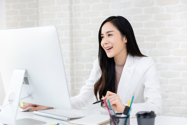 Szczęśliwy piękny azjatycki bizneswoman pracuje na komputerze w biurze Premium Zdjęcia