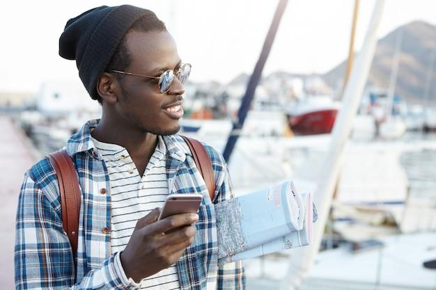 Szczęśliwy Podekscytowany Afroamerykański Podróżnik Z Plecakiem W Stylowych Okularach Przeciwsłonecznych I Kapeluszu Trzymający Papierową Mapę Pod Pachą, Korzystający Z Aplikacji Do Nawigacji Online Na Telefonie Komórkowym Przed Podróżą Darmowe Zdjęcia