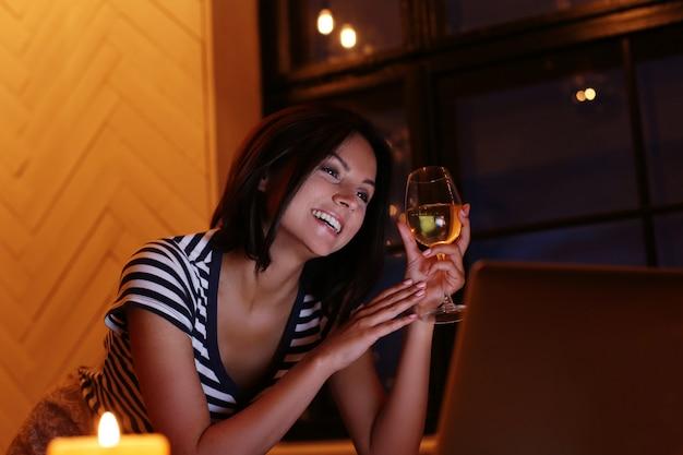 Szczęśliwy Portret Kobiety Przy Lampce Wina, Patrząc Na Ekran Komputera Darmowe Zdjęcia