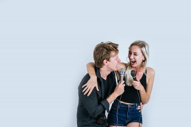 Szczęśliwy portret pary mienia mikrofon i śpiewa piosenkę Darmowe Zdjęcia