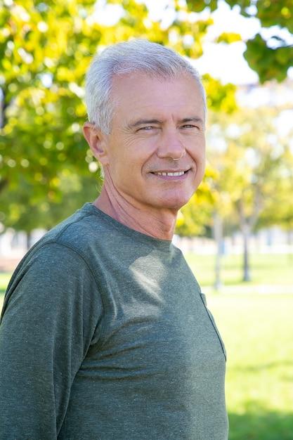 Szczęśliwy Pozytywny Dojrzały Mężczyzna Ubrany W Sportową Koszulkę Z Długim Rękawem, Stojący Na Zewnątrz I Uśmiechnięty. Sredni Strzał. Dojrzała Sportowa Osoba Lub Koncepcja Aktywnego Stylu życia Darmowe Zdjęcia