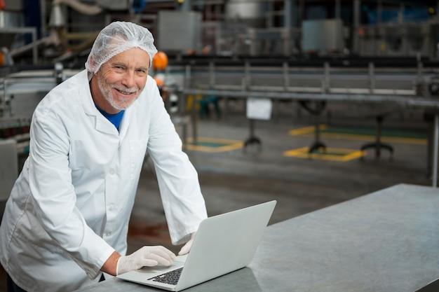 Szczęśliwy Pracownik Płci Męskiej Za Pomocą Laptopa W Fabryce Darmowe Zdjęcia