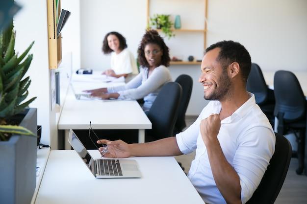 Szczęśliwy profesjonalny siedzący w miejscu pracy Darmowe Zdjęcia