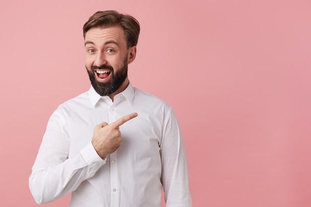 Szczęśliwy Przystojny Brodaty Młody Człowiek, Ubrany W Białą Koszulę. Chce Przekazać Wspaniałe Wiadomości. Szeroko Uśmiechnięta, Zwraca Twoją Uwagę, Wskazując Na Miejsce Po Prawej Stronie, Odizolowane Na Różowym Tle. Darmowe Zdjęcia
