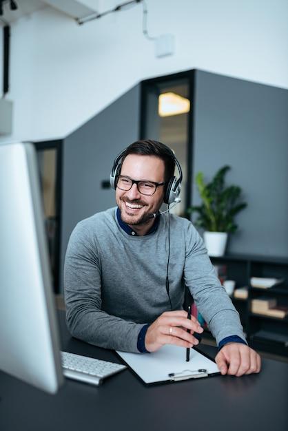 Szczęśliwy Przystojny Technika Kierownik Opowiada Z Klientem Na Słuchawki. Premium Zdjęcia